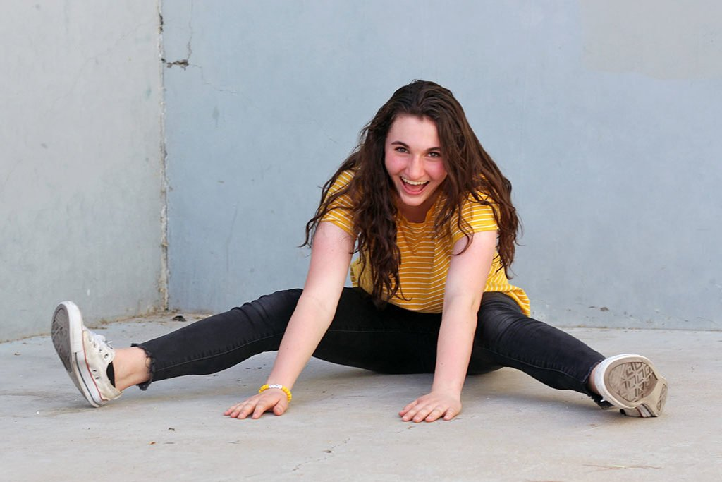 Attalie Anne Laughing while sitting on concrete